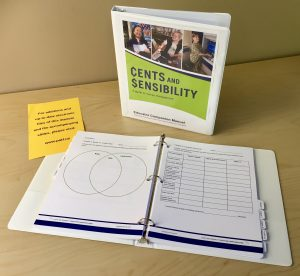White binder stands upright on a table. The cover reads Cents and Sensibility: A guide to money management, Educator Companion Manual. In front of it lays a white binder opened up to a spread showing two different activities, one with a venn diagram, the other with a grid of spaces to fill in. The binder includes chapter tabs and a yellow sheet at the front sticking out that reads For additions and up-to-date electronic files of this manual and the accompanying slides, please visit: www.patf.us.