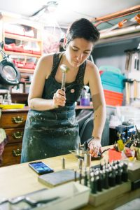 Rea is hammering metal with her cell phone next to her in her studio.