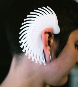 "Rea displays her wearable sculpture ""Cilia"", a white formation that fits over her ear."