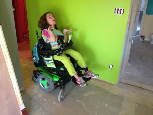 Alexa sits in her wheelchair in her new home in front of a bright green wall.