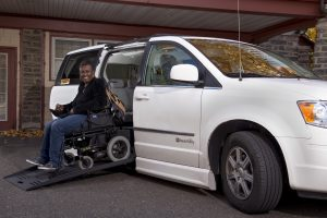 A woman drive her power wheelchair down the ramp of an adapted minivan.