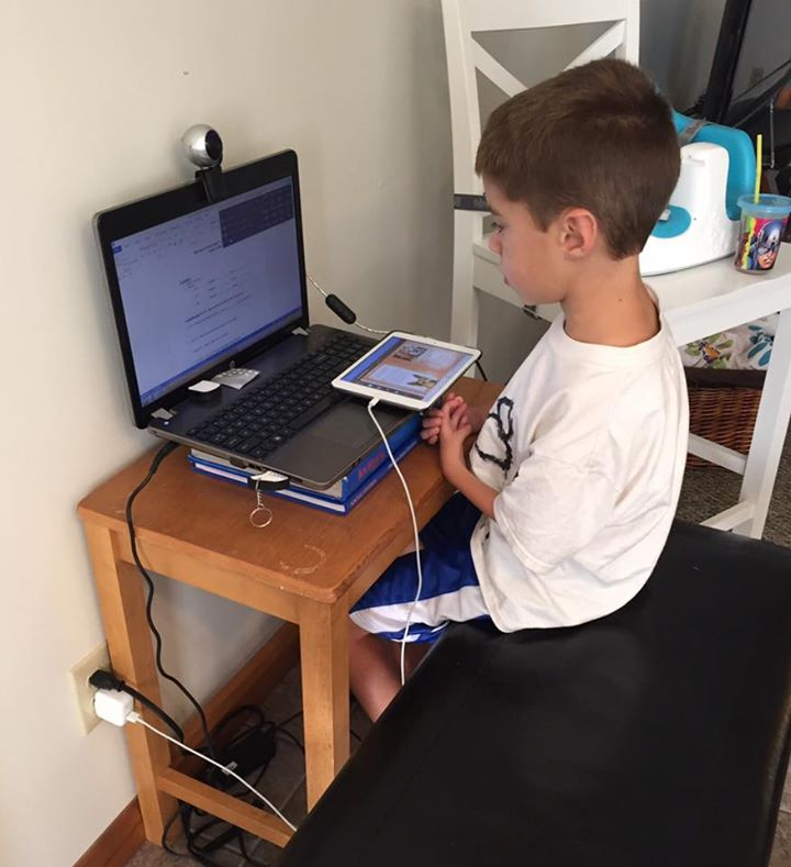 Young boy sits at a computer with his iPad.
