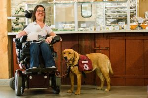 Linzey poses in a cafe with a red labrador retriever wearing a service dog vest.