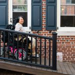 Suria drives her power wheelchair down her ramp in front of her Philadelphia townhouse.