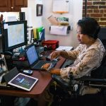Suria works at her computer using a desktop and a tablet.
