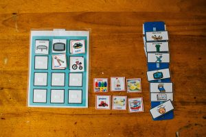 Three sets of PECS images laid out on a table with a variety of options including activities like biking and painting and food like cheese and grapes.
