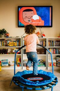 Penelope jumps on a trampoline while watching TV.