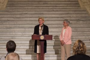 Holly Chase, of PHFA, speaks to a crowd from the podium with Susan Tachau next to her.