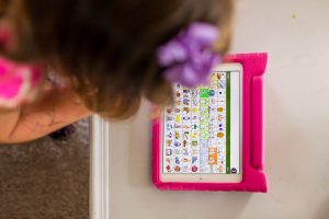 "View over girl's shoulder of iPad screen showing a grid of squares that each contain an image and word. For example, one square has a drawing of a smiling face and the word ""yes"" above it."