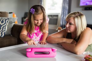 Young girl leans over iPad, tapping the screen with her finger while her mom sits next to her watching.