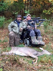 Two men smile at the camera, one of which is sitting in a power chair with a gun mounted on it and a deer laying in front.