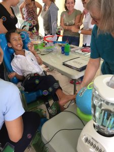 Boy sitting in a wheelchair grins widely while bubbles blow out of a round, blue bubble machine toward him.
