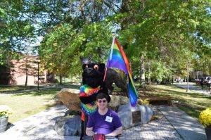 Man sits outside on a scooter in front of black panther mascot that is holding a rainbow flag and wearing a rainbow tie-dye tshirt.