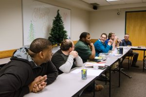 "Six men sit at long folding tables in a classroom with a whiteboard behind them that reads ""Happy Holidays"" and Christmas tree decoration behind them. One of the men in the center is talking, the others lean in with elbows on the tables, watching, listening and smiling."
