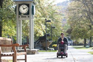On a sunny fall day, a man rides scooter along paved path on college campus with a bench in the foreground, and a clock tower and panther statue behind him.