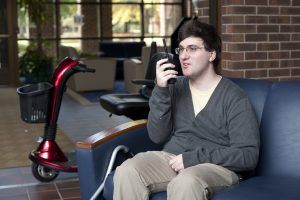 Man sits on blue couch in common area at college campus holding a two-way ham radio.