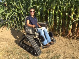 Woman sits in an all-terrain power wheelchair in front of a row of corn.
