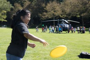 A girl tosses a yellow frisbee in a grassy field. There is a helicopter in the background with a crowd around it.