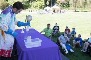 A man in a tie dye lab coat stands behind a table in the grass performing a science experiment for a small audience of all ages, some of whom are using wheelchairs.