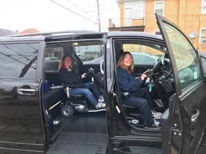 Two women sit on their scooters in their adapted van, one in the front passenger area, the other in the rear passenger area.