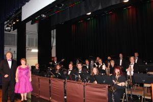 A full swing band seated on risers on a stage.