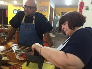 Woman and man wearing aprons stand at a table preparing salsa.