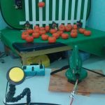 A large yellow switch, connected by a cord to a leaf blower that is strapped to a table and aimed at a pile of small plastic orange pumpkins.