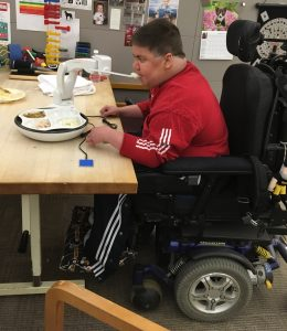 Man sits at desk in power wheelchair eating food off the fork of a robotic arm positioned on the table.