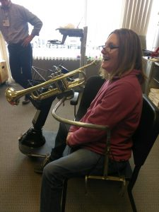 Woman sits in a musician's chair with a trumpet in front of her, smiling at her bandmates. The trumpet is suspended by a metal arm that extends from the seat of her chair.