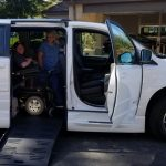 Man in power wheelchair inside adapted van with door open and ramp extended. Woman stands inside the van with him and another stands outside, all smiling.