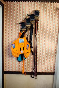 Clovers packed backpack, leash, and other equipment hanging on a set of hooks on the wall.