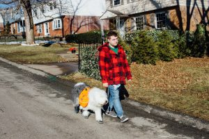 Sam and Clover walk down a suburban street.