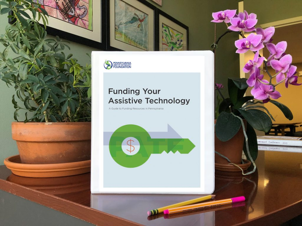 A binder with the words, Funding Your Assistive Technology, on the cover and an image of a dollar sign and a key is propped on an office desk with plants behind it and pens laying in front of it.