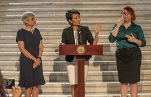 Senator Patti Kim speaks at the press conference with PATF CEO Susan Tachau at her side, and an ASL interpreter at her other side.