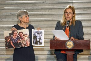 PATF CEO Susan Tachau holds up two photos of a young woman using a wheelchair next to Senator Melissa Shusterman who speaks to the audience at a podium.