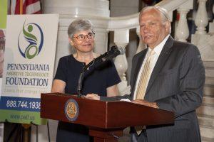 State Senator Bob Mensch speaks at a podium while PATF CEO Susan Tachau looks on.