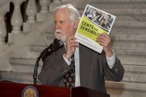 PATF Board member David Gates holds up Cents and Sensibility, PATF's financial education book.