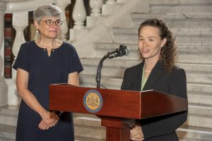 PATF CEO Susan Tachau looks on as Abbie Spackman of AgrAbility PA speaks to the audience at a podium.