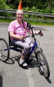 Young woman smiles while riding a handcycle on a paved road with lush greenery in the background.
