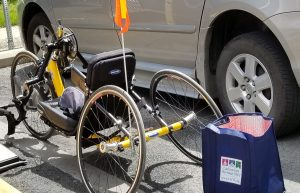 "Yellow handcycle parked next to a car. Handcycle has an orange flag on the back and a shopping bag that says ""Lackawanna Heritage Valley, www.LVHA.org"" on it."