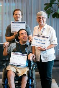 Two men, one seated in a wheelchair, and his mother smile and hold signs that read Financial empowerment is... with handwritten answers.