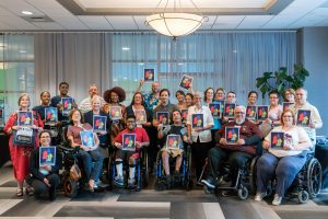 "18 people smiling and holding signs with arrows pointing to their faces that read ""This is the face of #FinancialEmpowermentForPWD"""