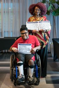 Mother and son, who is seated in a wheelchair, smile and hold signs that read Financial empowerment is... with handwritten answers.