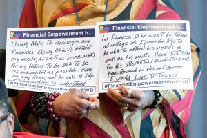 Close up of woman's hands holding two signs that read Financial Empowerment is... with handwritten answers.