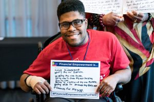 Young man, seated in a wheelchair, smiles and holds a sign that reads Financial Empowerment is... with a handwritten answer.