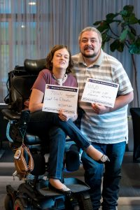 Woman, who is seated in a wheelchair, and man smile holding signs that read Financial Empowerment is... with handwritten answers