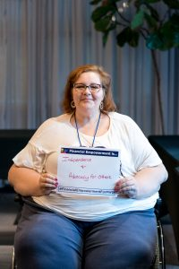 Woman smiles, seated in a wheelchair, and holds a sign that reads Financial Empowerment is... with a handwritten answer.