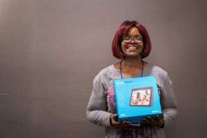 TaMara Terry smiles, holding up her Amazon Echo Show box.