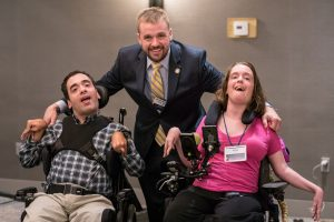 Michael Anderson and Alexa Brill, both wheelchair users, smile with Bryan Cutler who is standing in the middle with his arms around each.