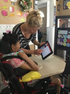 Brielle sits in her power wheelchair looking at a tablet that a woman holds in front of her and points to. Another screen is positioned beyond the tablet displaying picture communication symbols.
